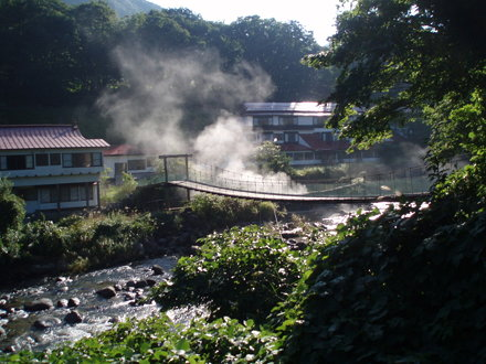 Takanoyu Onsen (鷹の湯温泉) from across the river (湯沢市; Yuzawa-shi) with steam rising from the hot spring