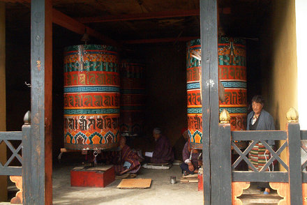 Elderly people turning the prayer wheels all day