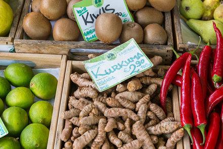 Obst und Gemüse in Holzkisten, mit mehreren Kurkumawurzeln, zwischen Chilischoten und Kiwis